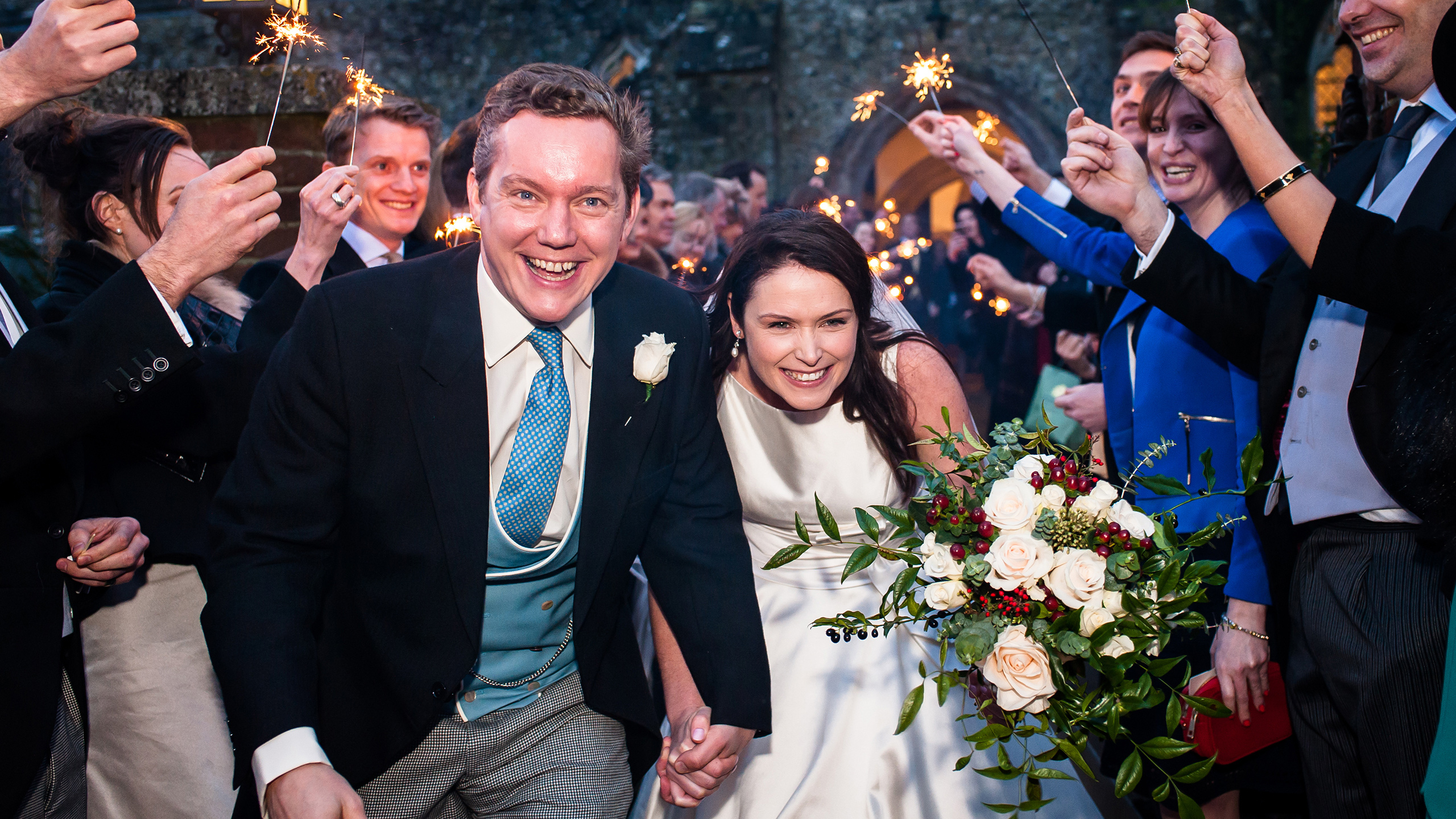 Photograph of Marcus and Frances leaving the church under guests with sparklers after their Kent ceremony