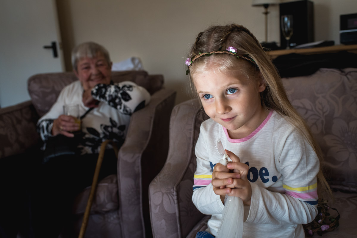 Little flower girl sits and waits during the bridal preparation at Lianne and Johns wedding at Lympne Castle in Kent
