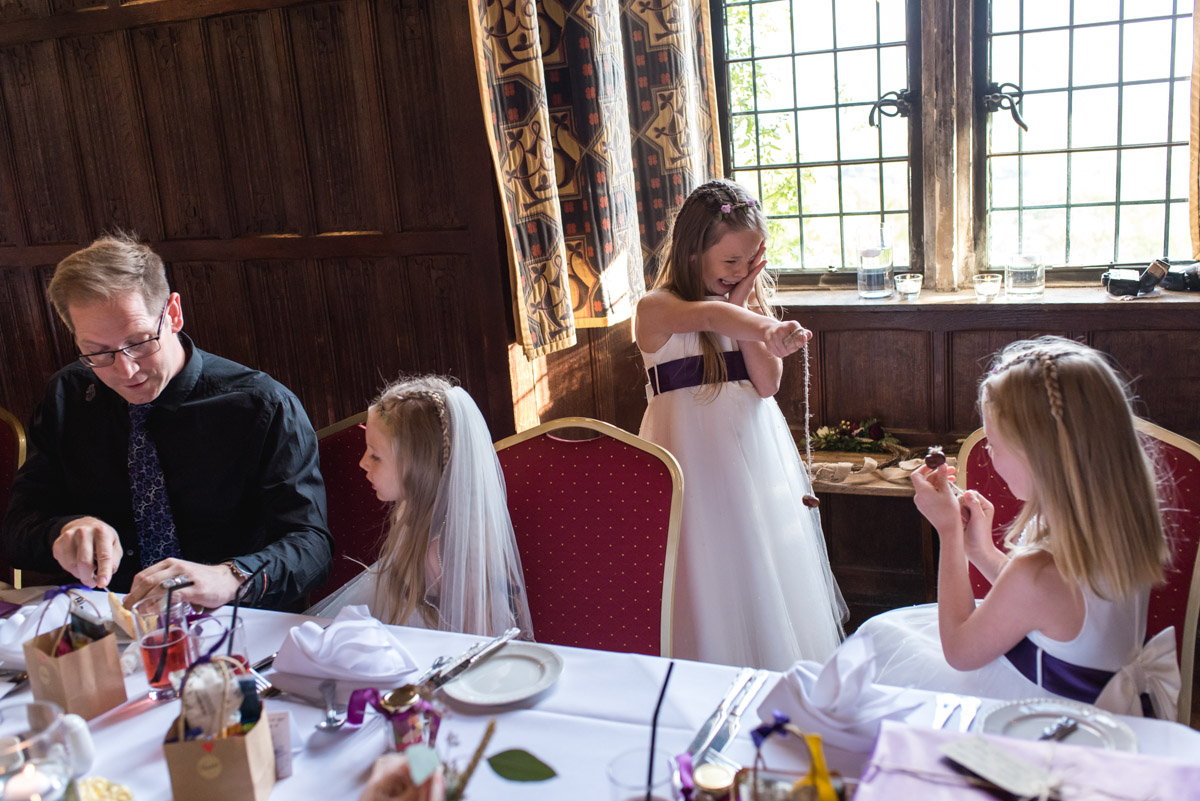 Flower girls are photographed playing conkers during Lianne and Johns Kent wedding at Lympne Castle In Kent