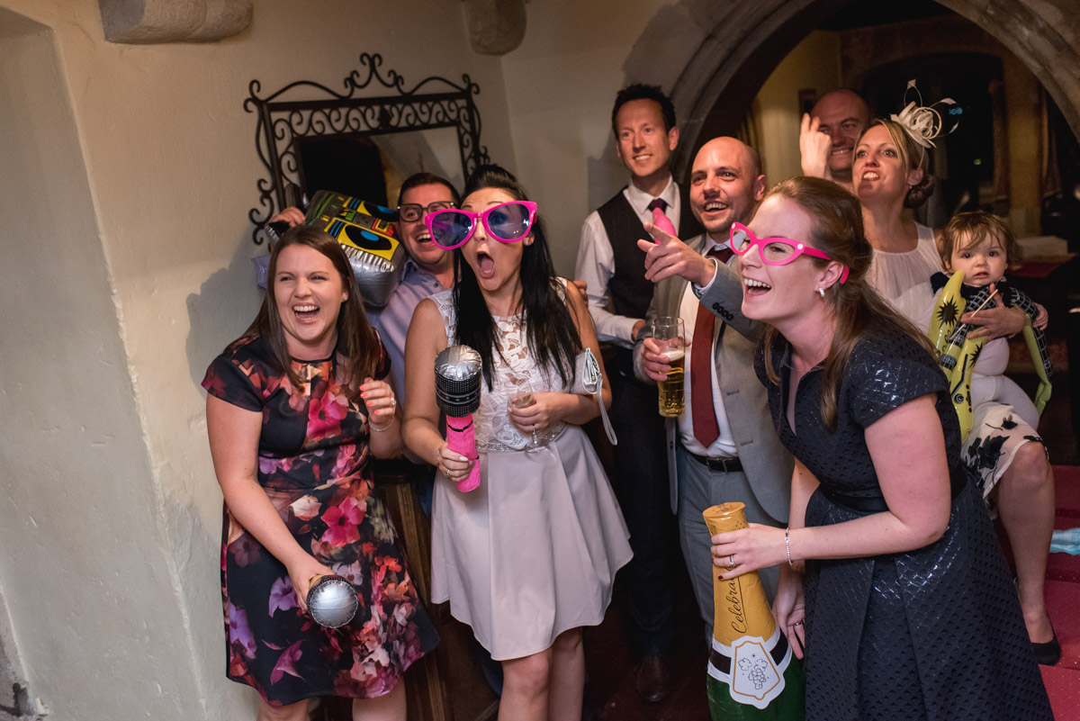 Photograph of wedding guests in funny props at Lianne and Johns reception at Lympne Castle in Kent