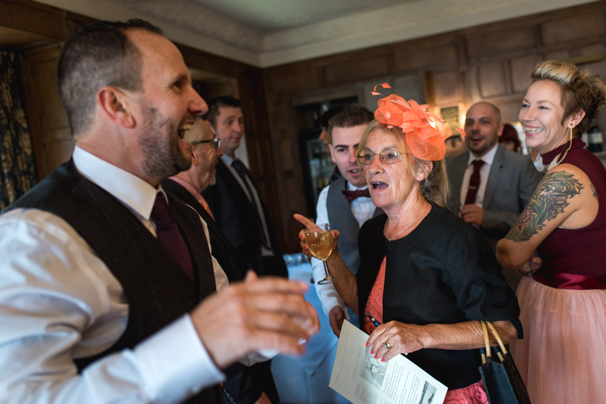Photograph of wedding guests and John in the bar at Lympne Castle before the ceremony