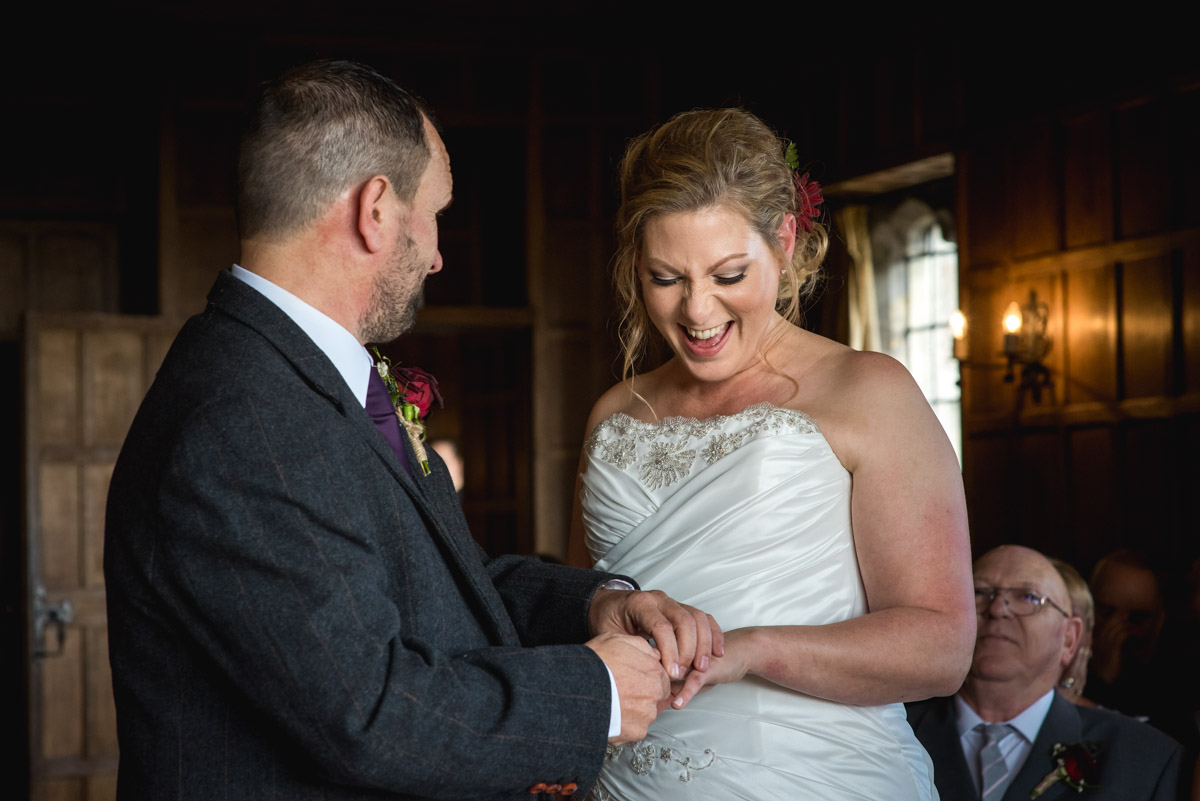 Photograph of John placing the ring on Liannes finger during their wedding at Lympne Castle in Kent