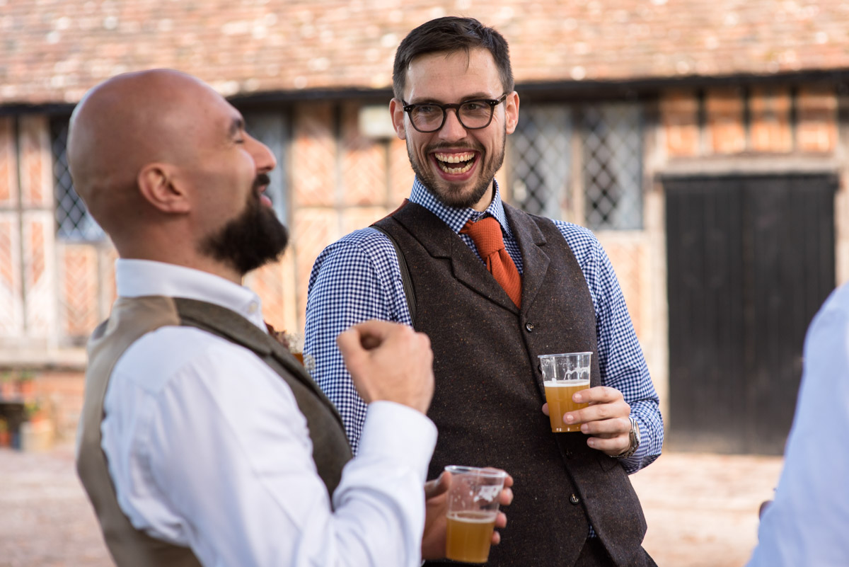 Paul laughs with groomsmen before his Kent wedding at Chilham Village Hall