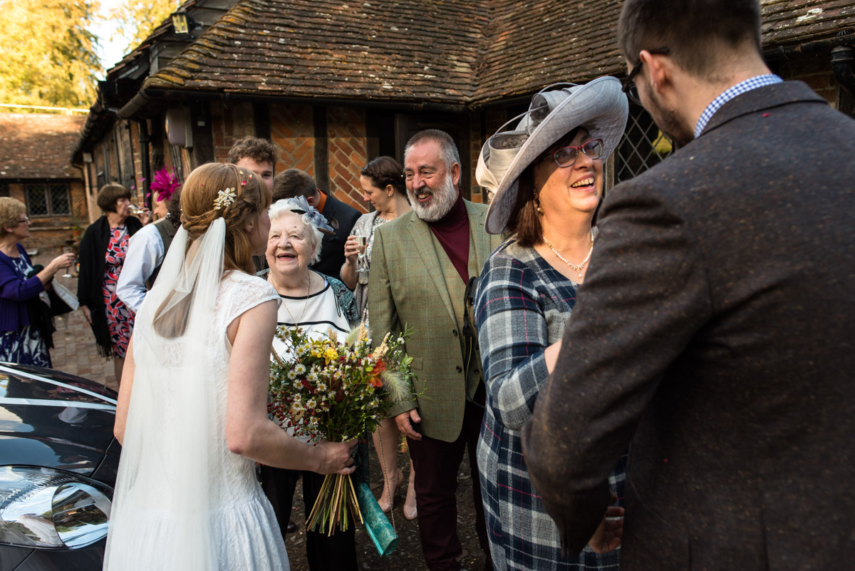 wedding guests at Chilham Village hall congratulate laura and Paul