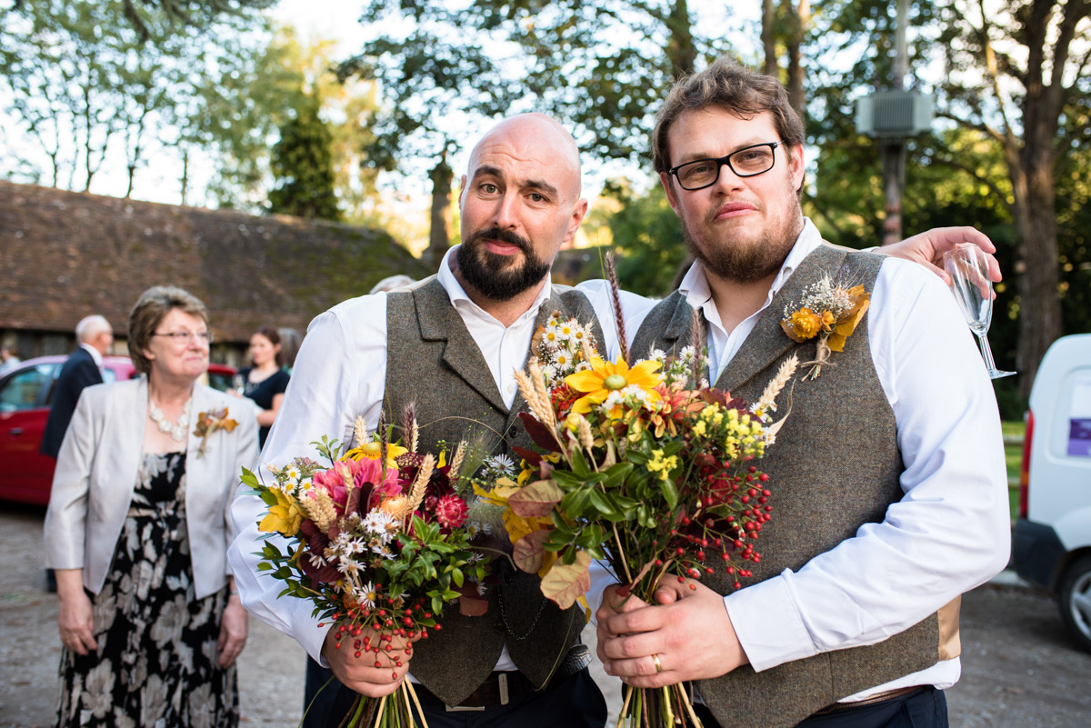 Groomsmen are photographed holding wedding flowers at Chilham Village Hall in kent