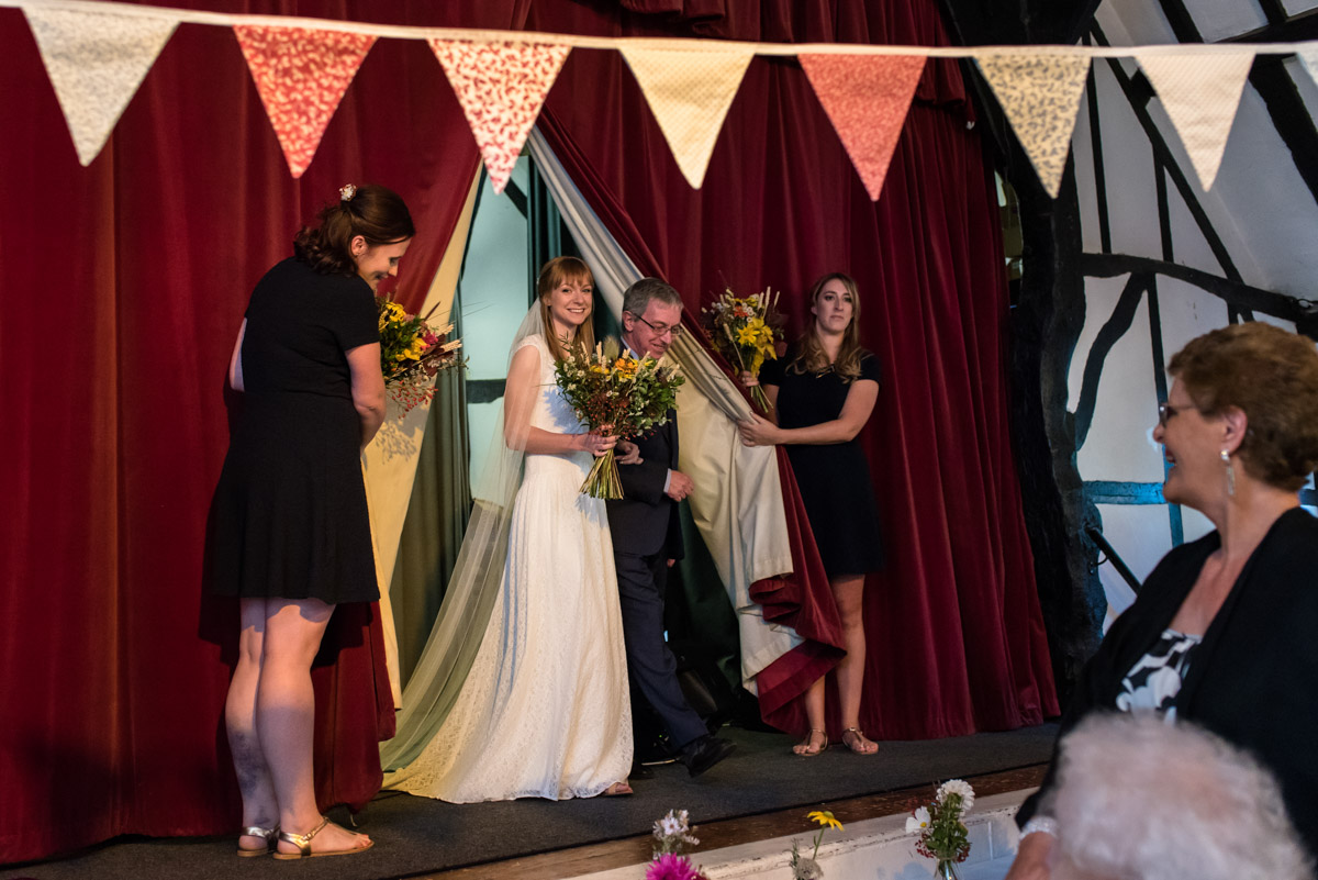 Laura and her bridesmaids are photographed on the stage before the wedding ceremony at Chilham Village hall in Kent