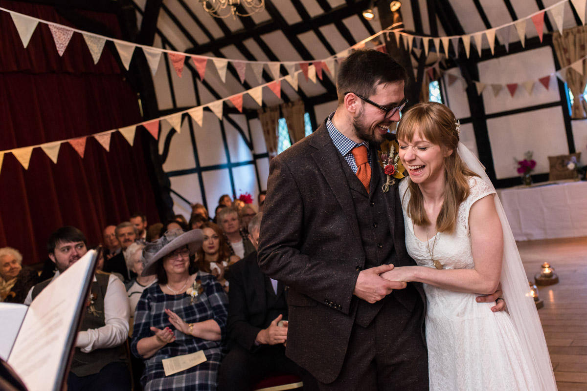 Laura and Paul are photographed sharing a joke after taking their wedding vows in kent venue Chilham Village Hall