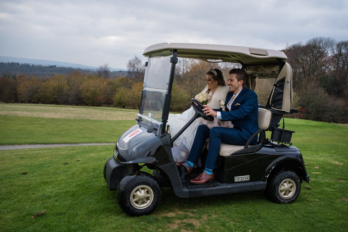 Photograph of Jade and Stuart driving golf buggy at their wedding reception