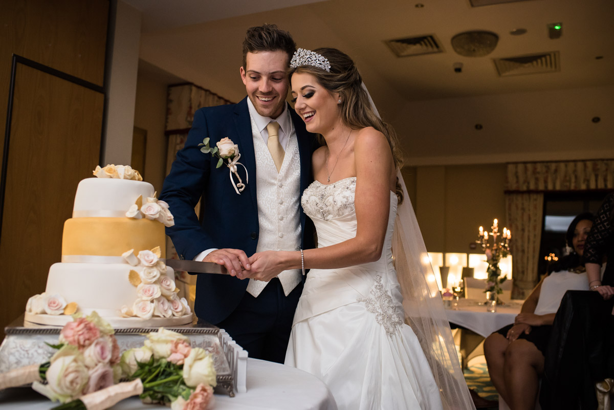 Jade and Stuart are photographed cutting their wedding cake