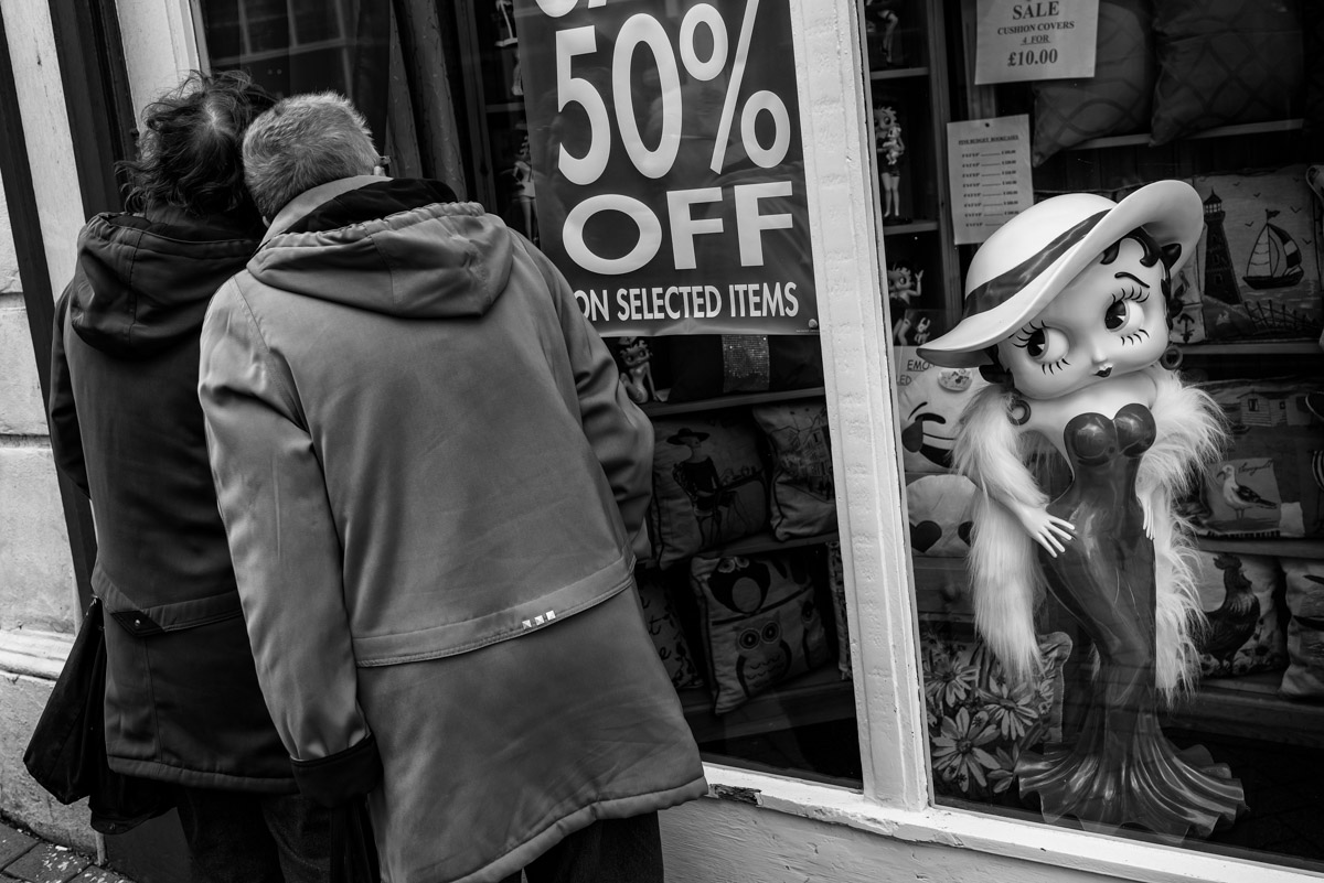 Black and white street photograph of Betty Boo and two ladies looking in shop window
