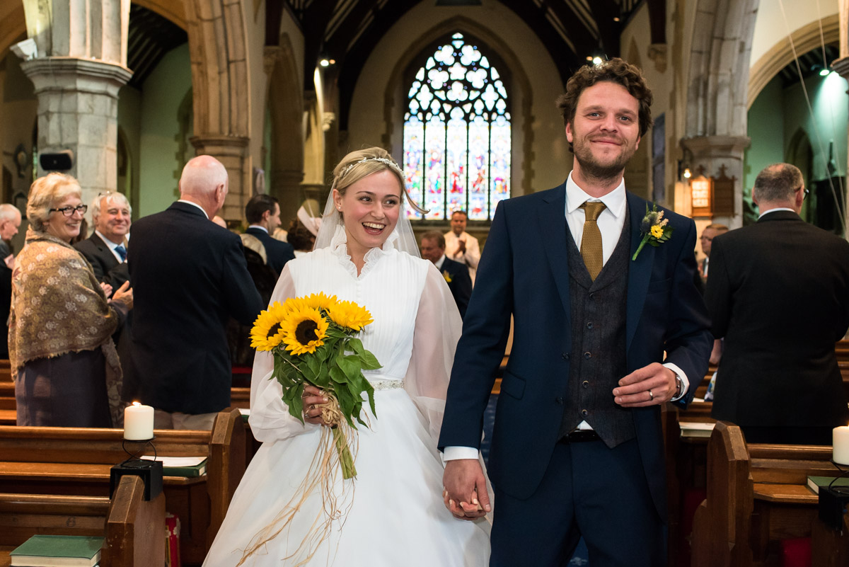 Photograph of Steven and Jane walking down the aisle after their chilham church wedding ceremony
