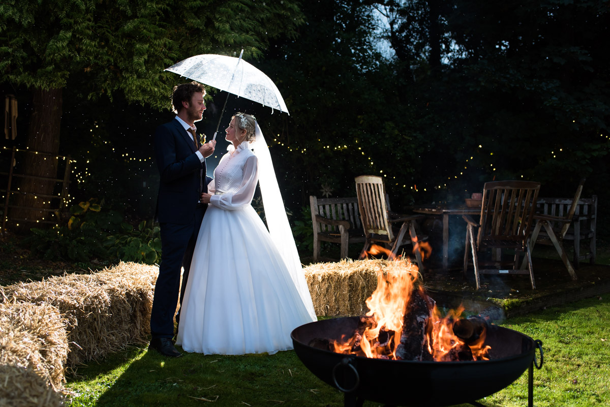 Night time portrait of Jane and Steven outside by the fire pit on their wedding day