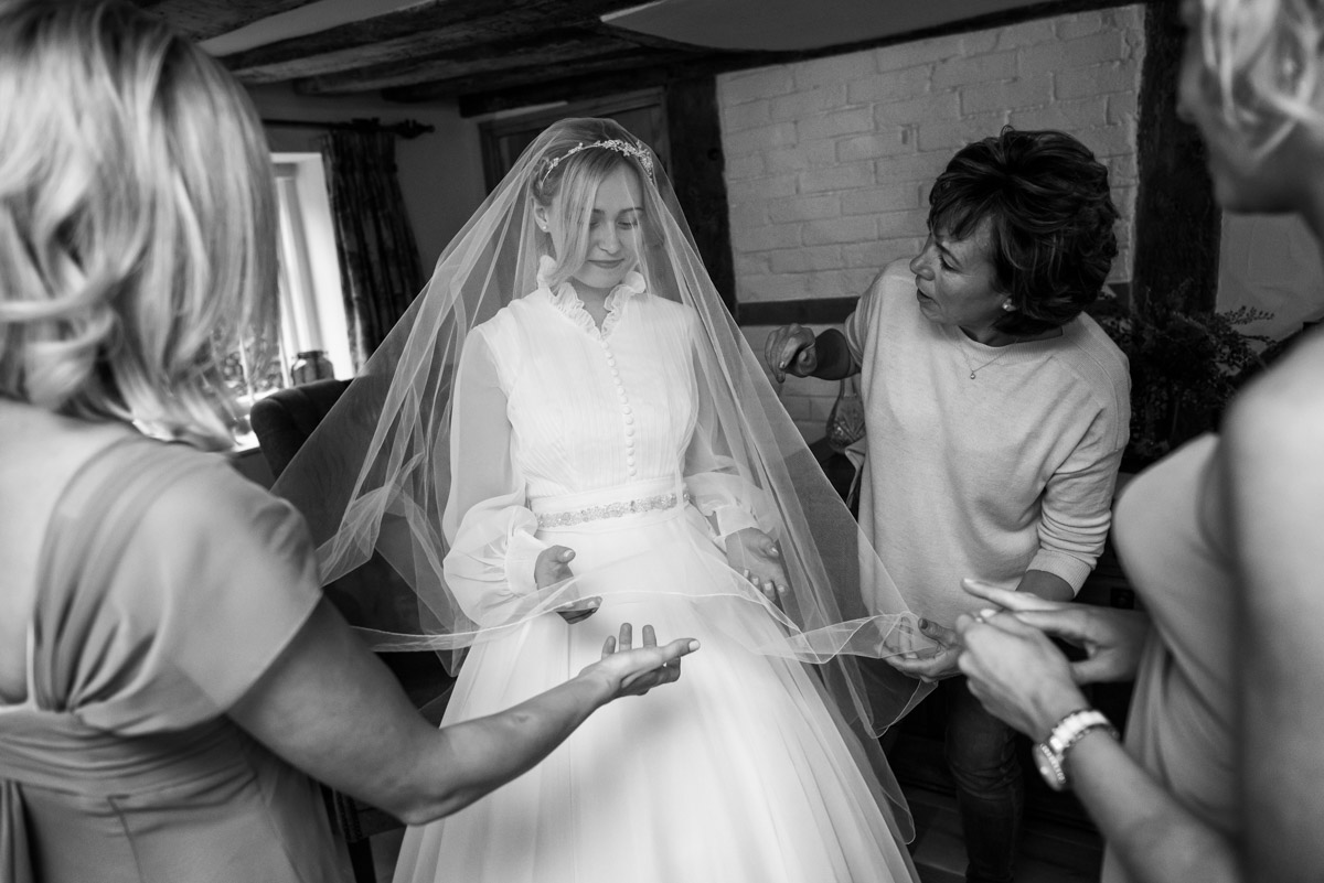 Photograph of Marissa and bridesmaids helping Jane with her veil on her wedding day