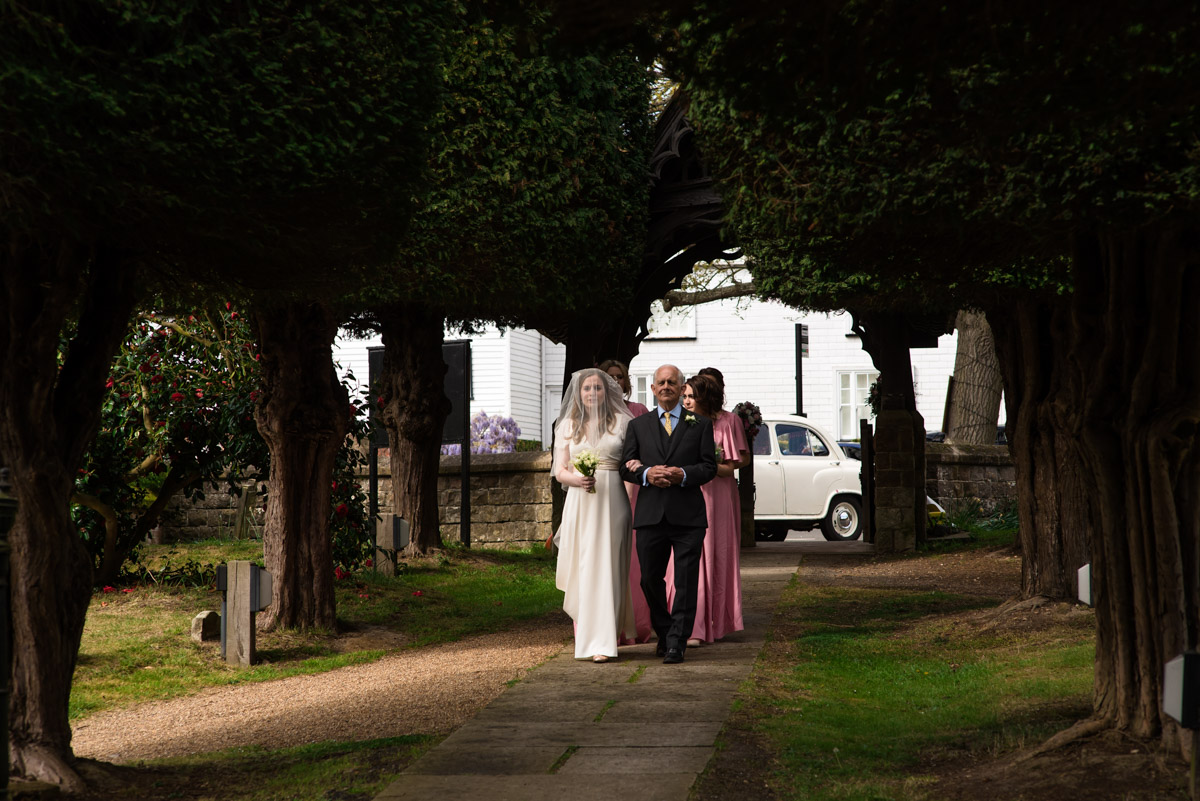 Flora and father walk down church path for wedding ceremony in Brenchley