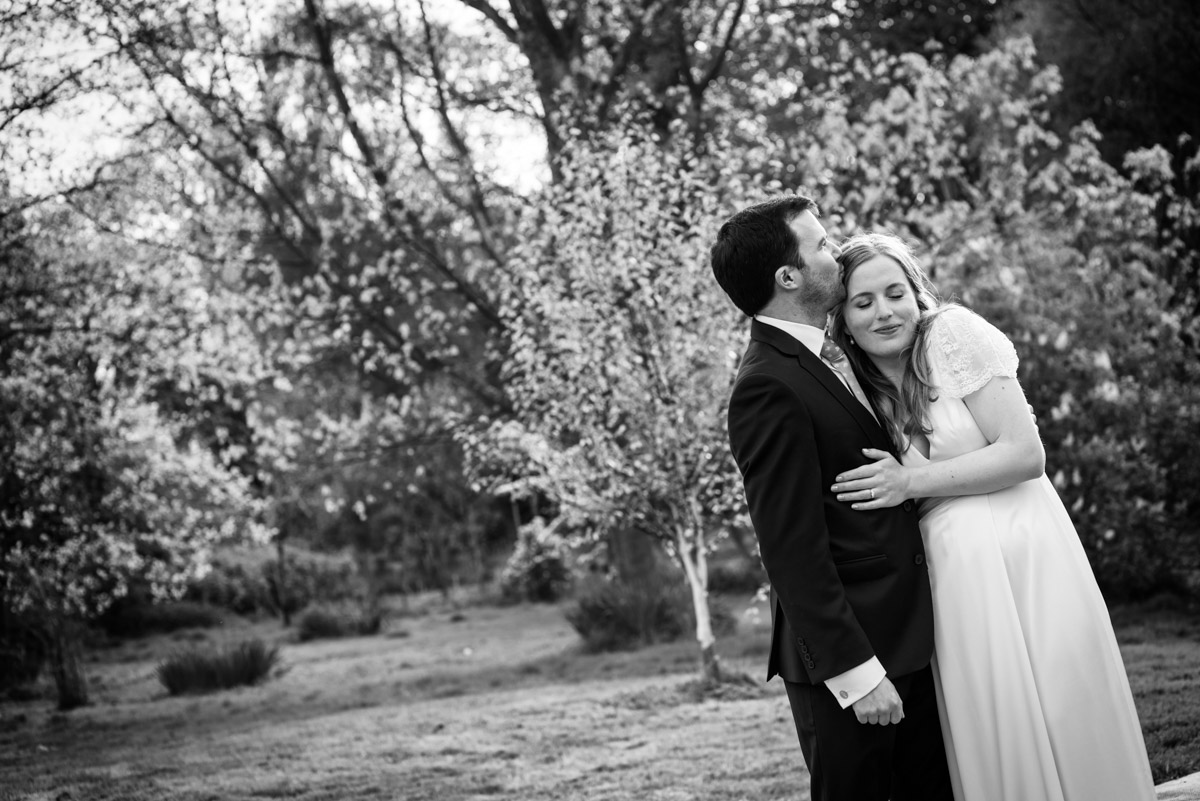 Black and white photograph of Flora and James in the garden of their wedding reception