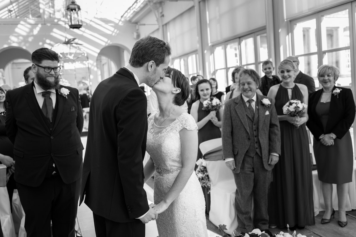 Black and white photograph of Joe and Bennets first kiss at Buxted park Hotel wedding