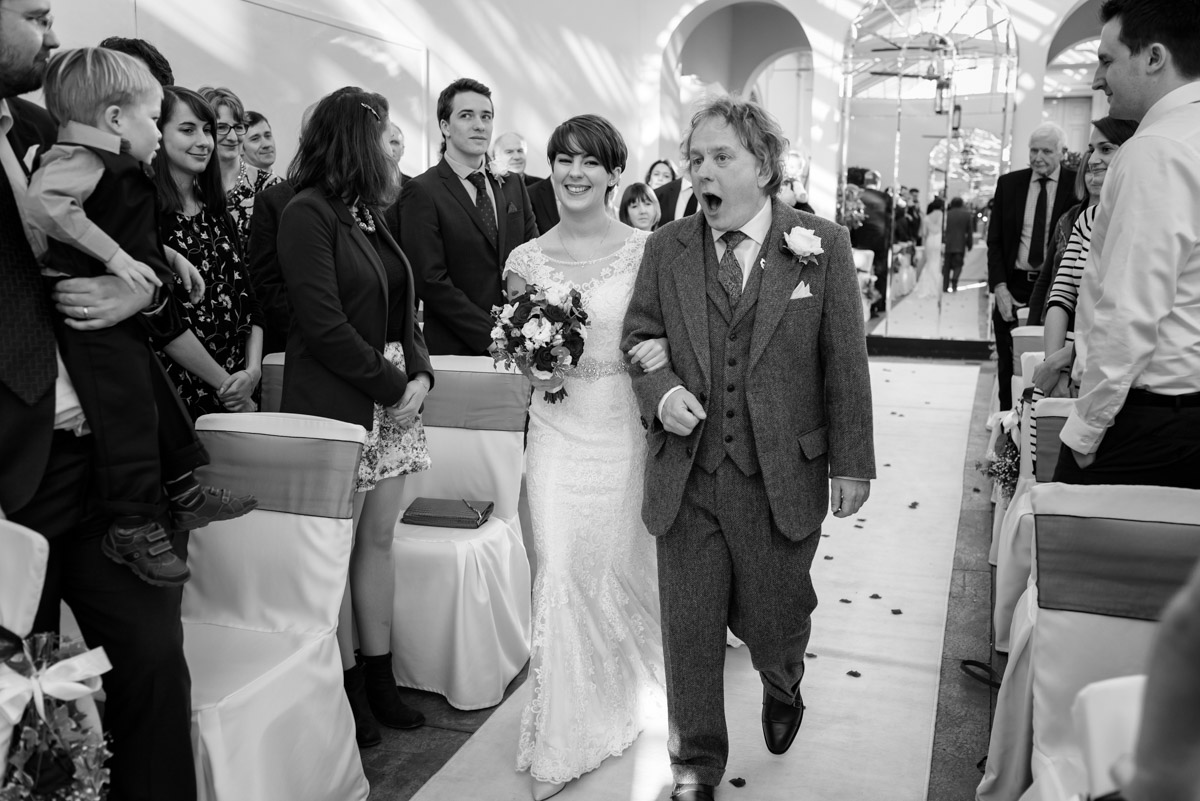 Father and daughter walk down the aisle at Buxted park Hotel wedding