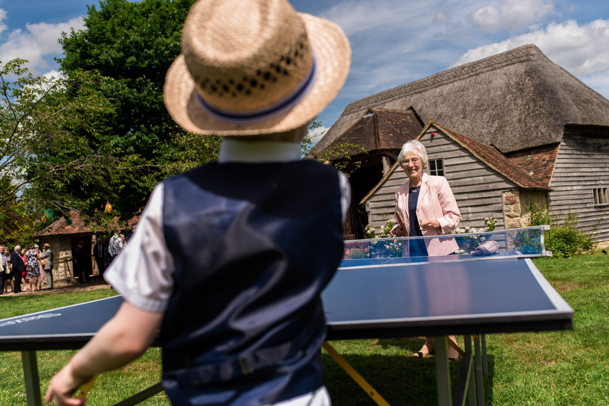 Wedding guests photographed playing table tennis in grounds at Ratsbury Barn