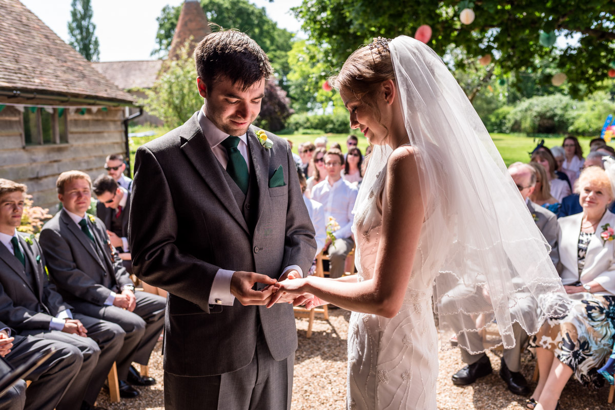 Tom places ring on Beths finger during Ratsbury Barn wedding in Kent
