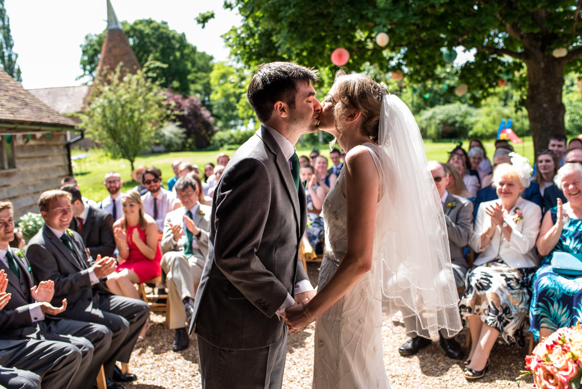 Beth and Toms first kiss photograph at their Ratsbury Barn wedding in Kent