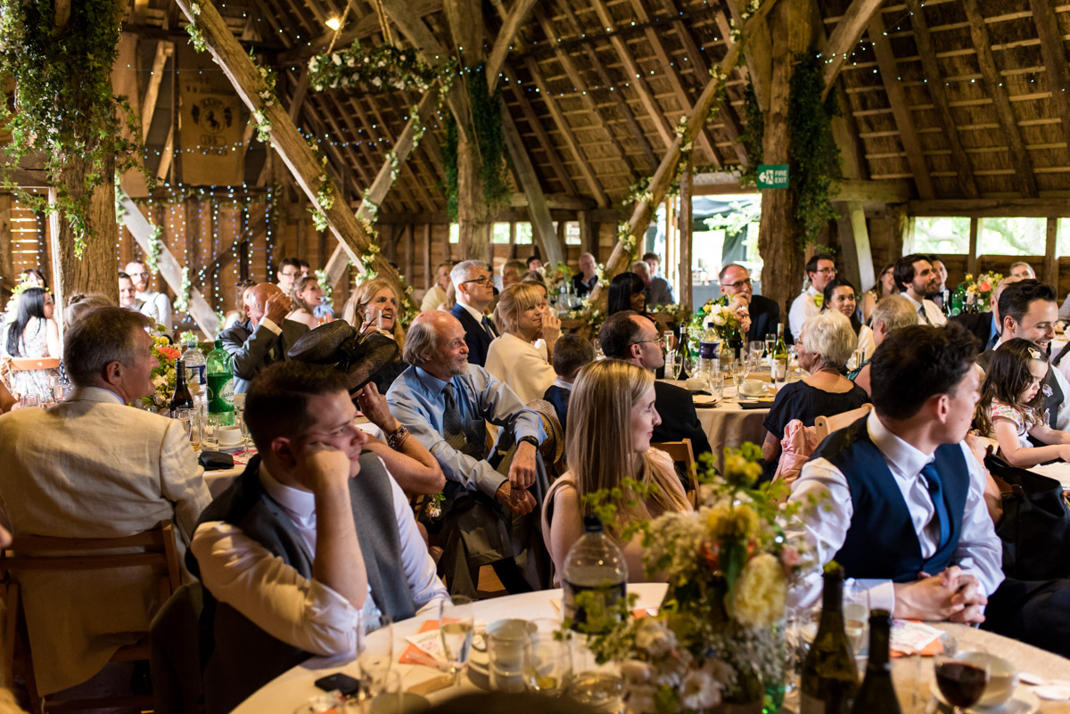 Photograph of wedding guests in Ratsbury Barn during Tom and Beth's reception