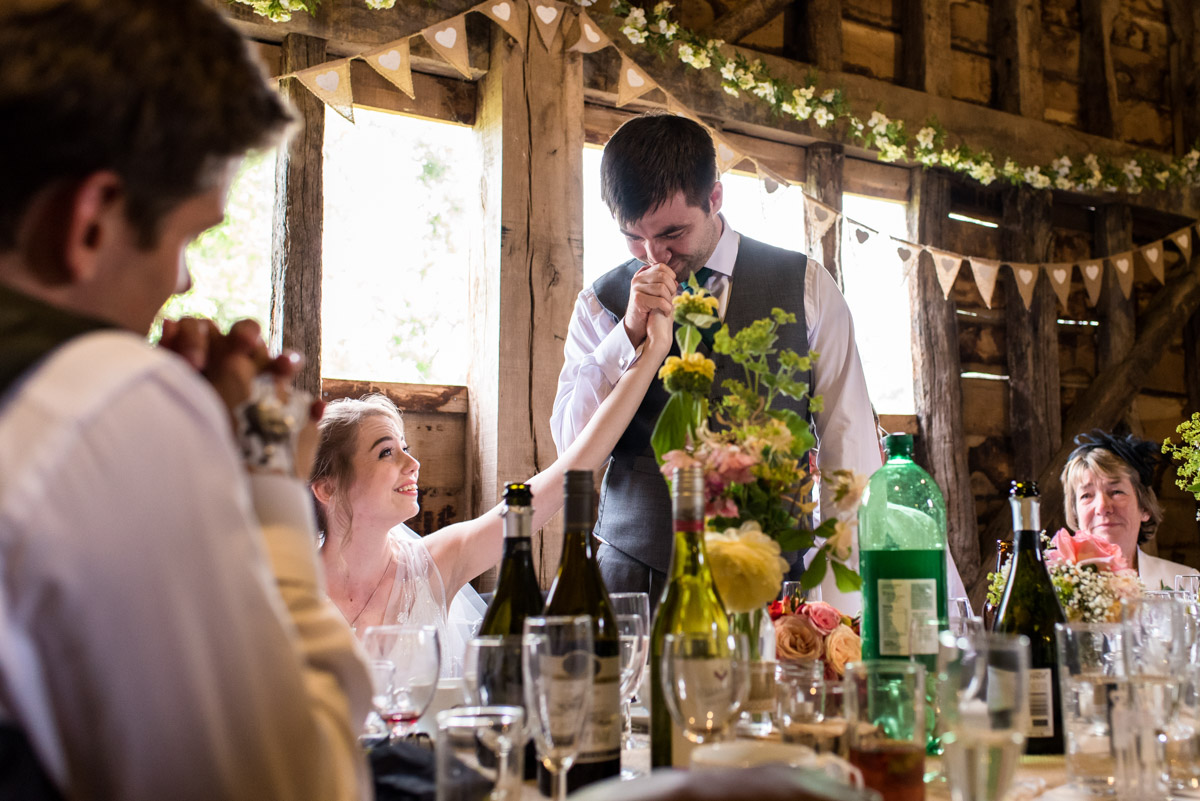 Tom kisses Beths hand after making his wedding speech at Ratsbury barn in Kent