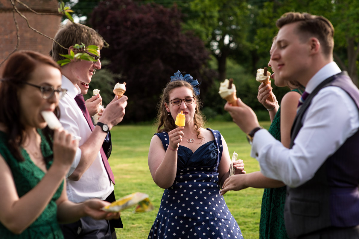 Wedding guests photographed eating ice creams at beth and Toms Ratsbury Barn wedding in Kent