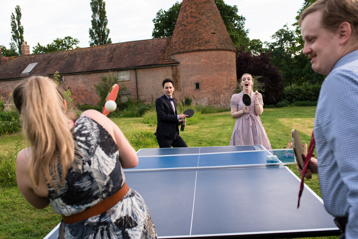 Photograph of beth and Toms wedding guests playing table tennis at Ratsbury Barn