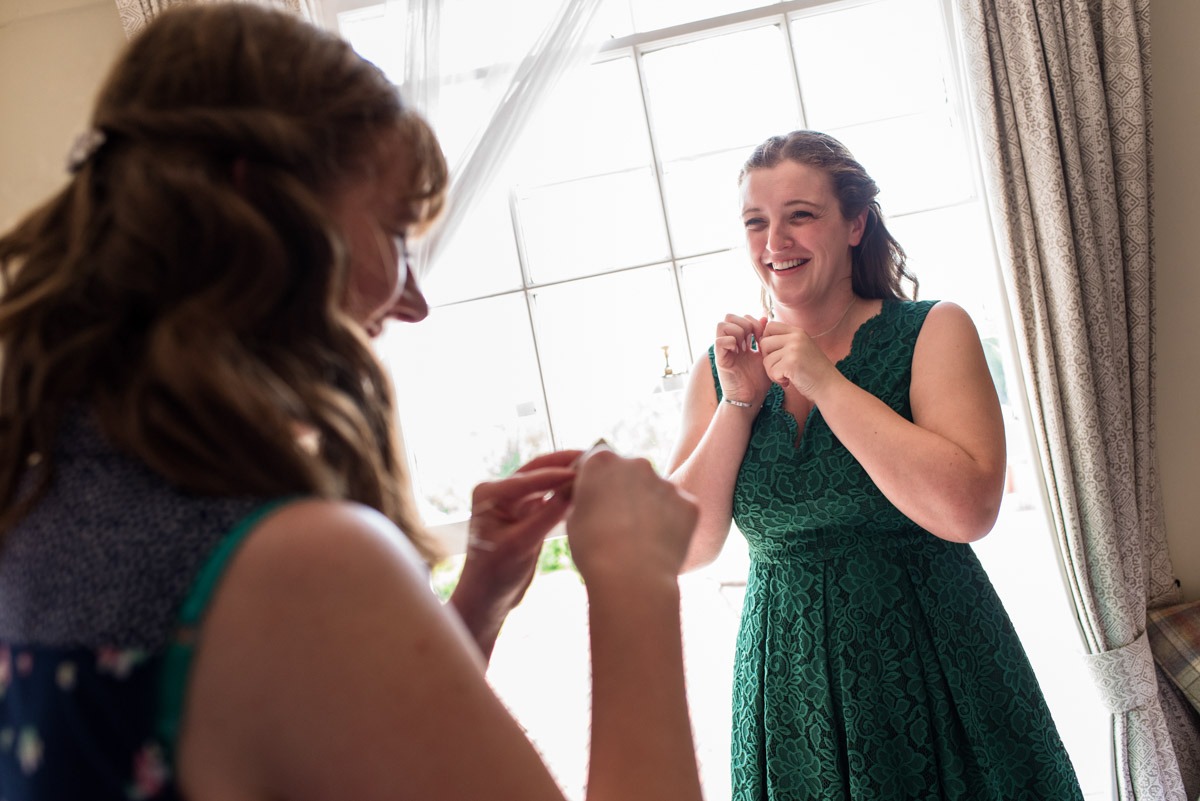 Bridesmaids put on neckless before Beth and Toms Ratsbury Barn wedding in Kent
