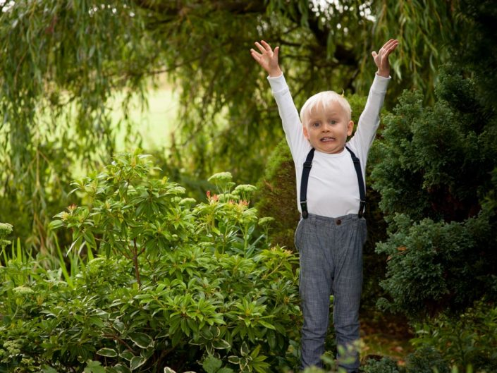 Natural outdoor portrait of small boy playing on garden rockery in Kent