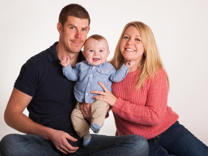 family studio photo with laughing baby boy in the middle taken by Kent photographer Helen Batt