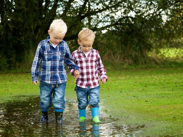 Harry and Jake outdoor portrait in Kent gardner walking through puddle