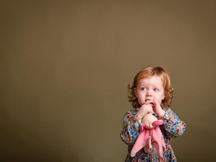 Kent Studio portrait of small girl chewing her cuddly toy