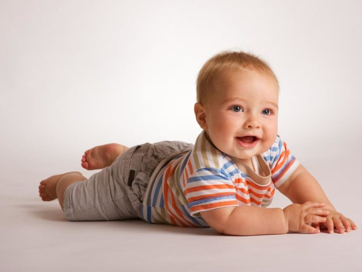 Studio portrait of baby Harry laughing at mum in Kent studio