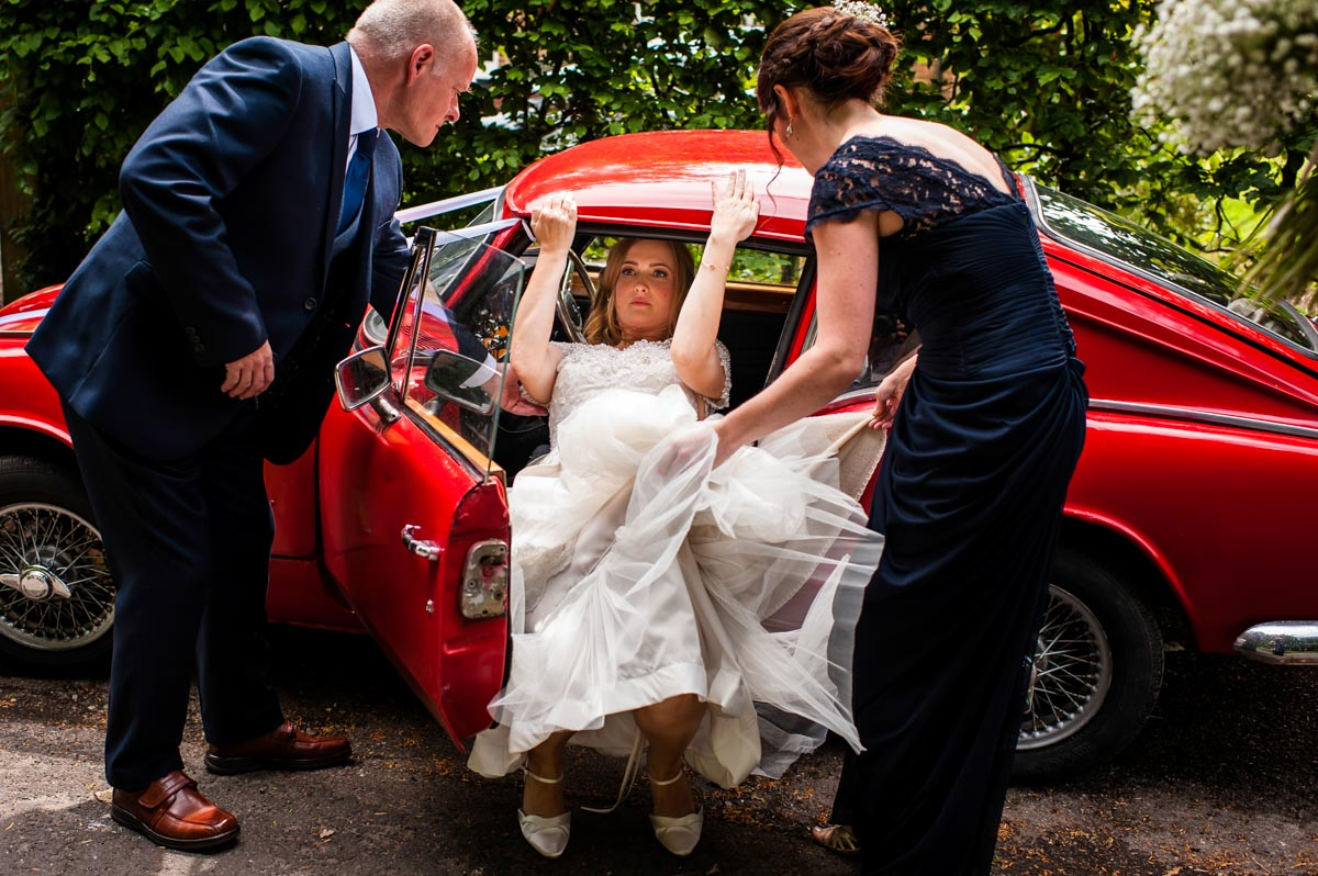 Bride exits from red sports car before her Kent wedding