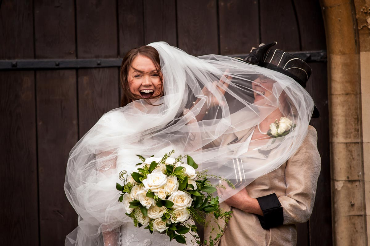 Photograph of veil blowing in brides mums face at kent church wedding