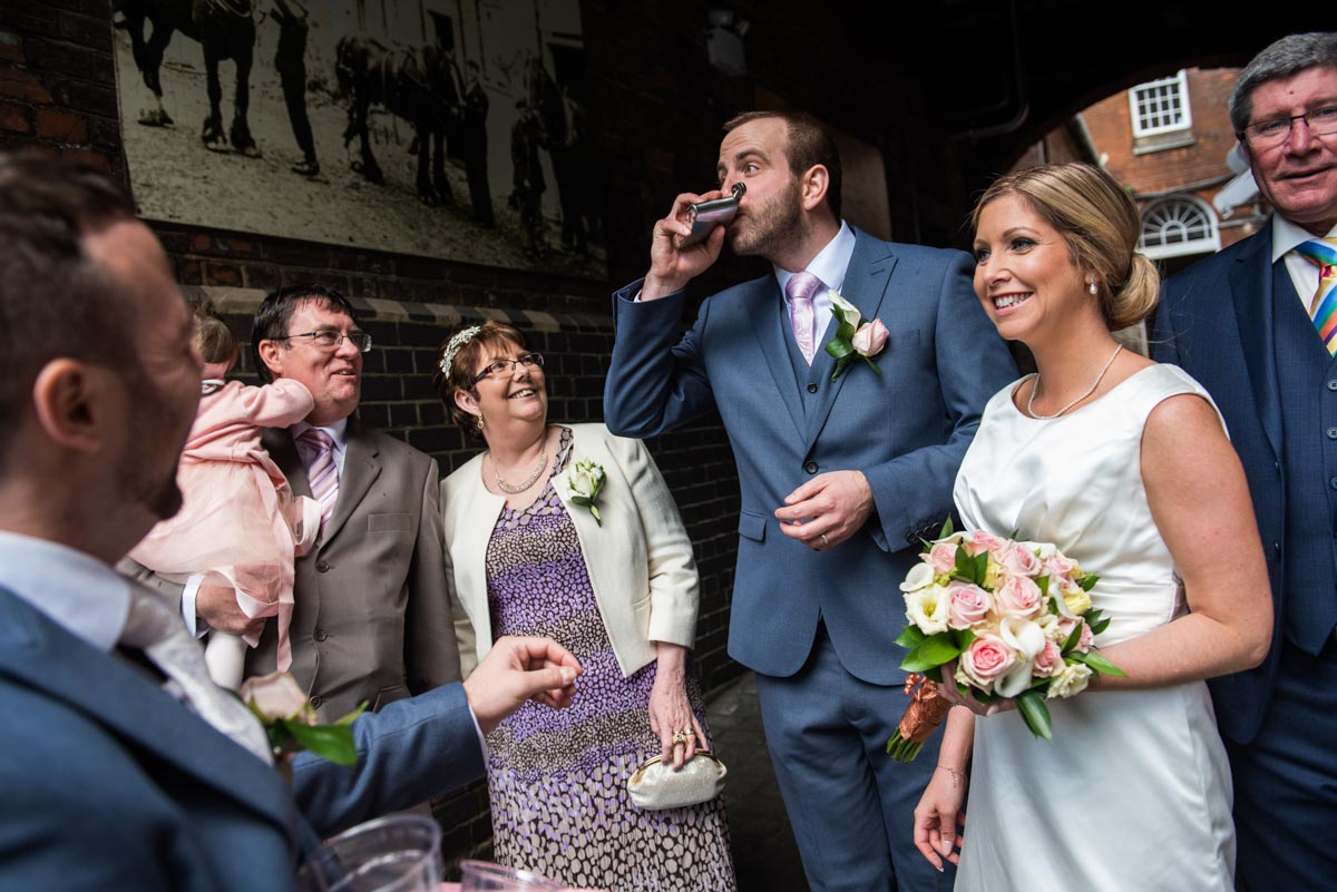Shepherd Neame weddding in Faversham. Groom drinks from hip flask