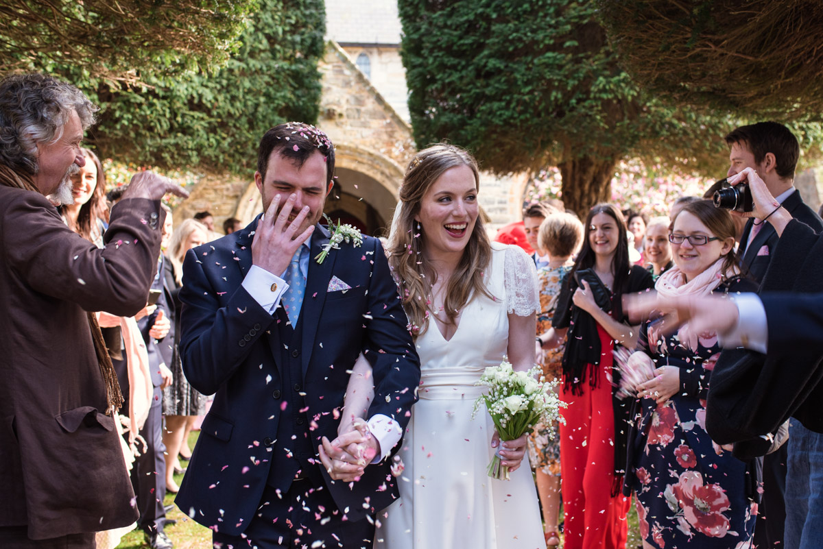 Flora and James photographed during confetti throw at their Kent wedding