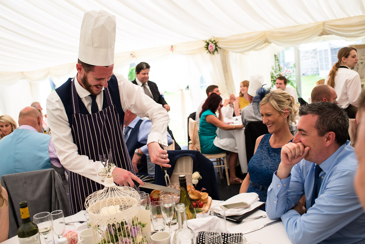 Guests at Paul and Lexys wedding are photographed during the wedding breakfast in the marquee in Kent