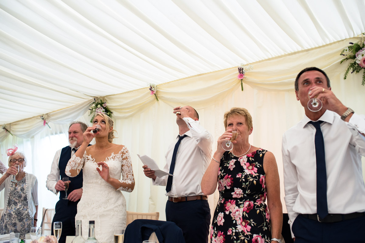 Toasting the wedding speeches with a drink at Paul and Lexy's Kent wedding