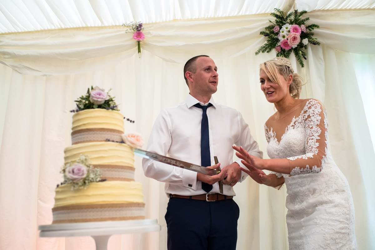 Traditional wedding photograph of paul and Lexy cutting their wedding cake