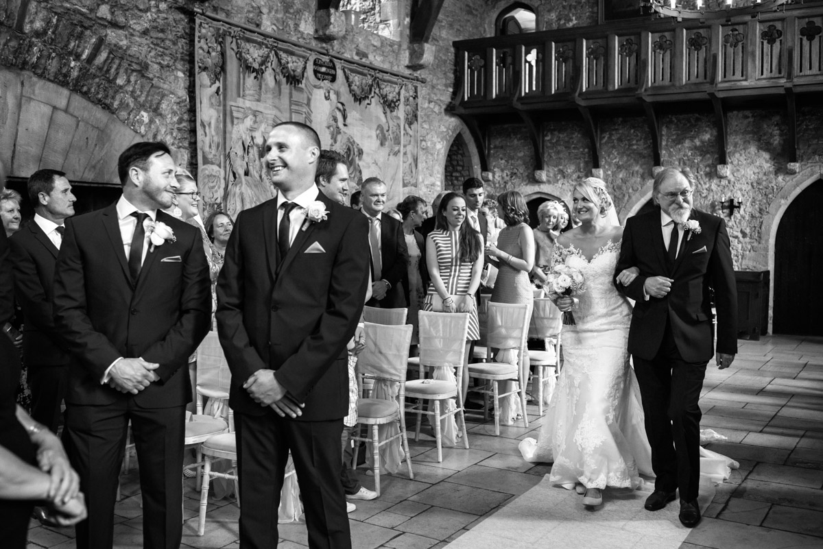 Black and white photograph of Lexy walking up the aisle in Allington Castle on her wedding day