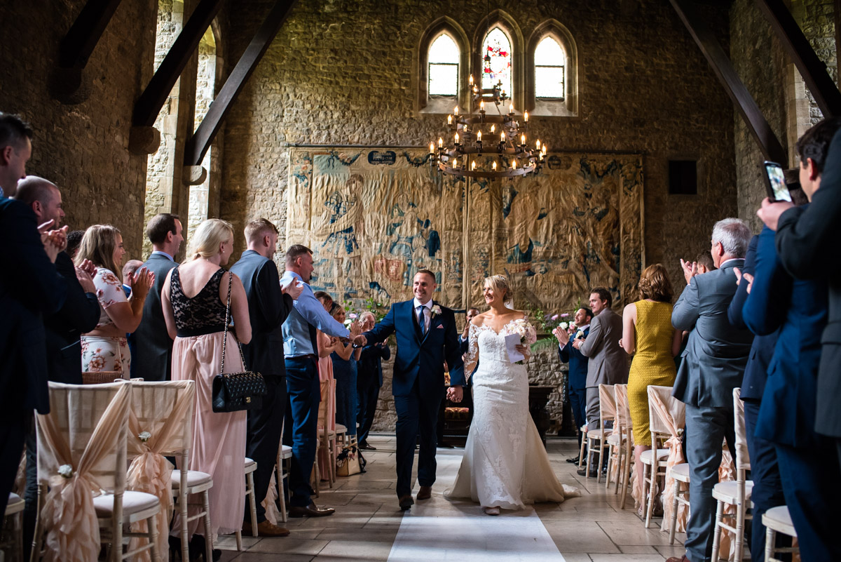 Paul & Lexy are photographed walking down the aisle after their ceremony in Allington Castle in Kent