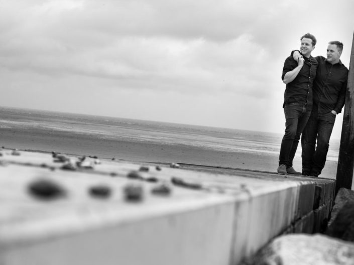Black and white photograph of David and Simon on the beach at Littlestone In Kent during their pre wedding photoshoot