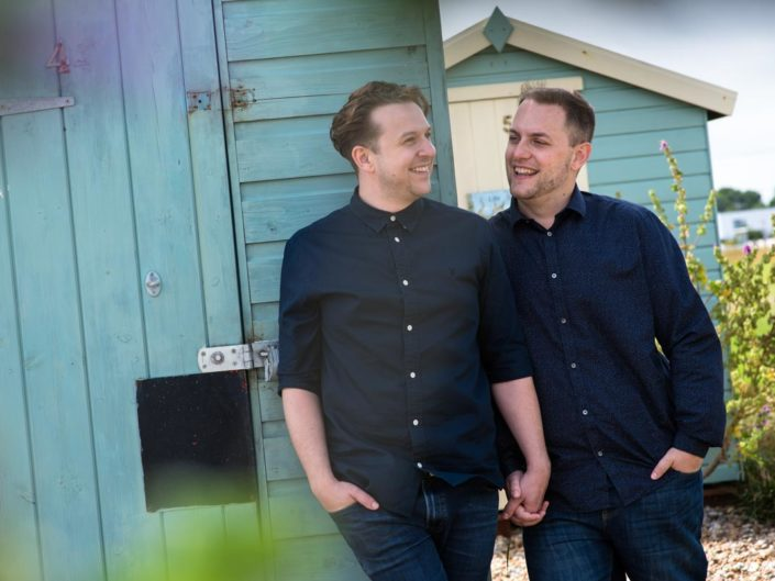 David and Simon are photographed by beach huts in Littleton, Kent during their engagement photo session