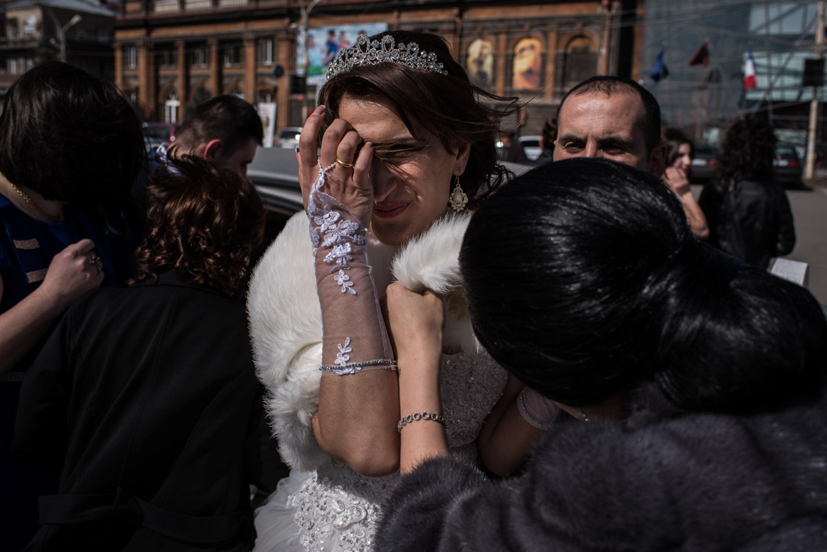 Armenian bride pushes hair from her face before going in for her wedding ceremony