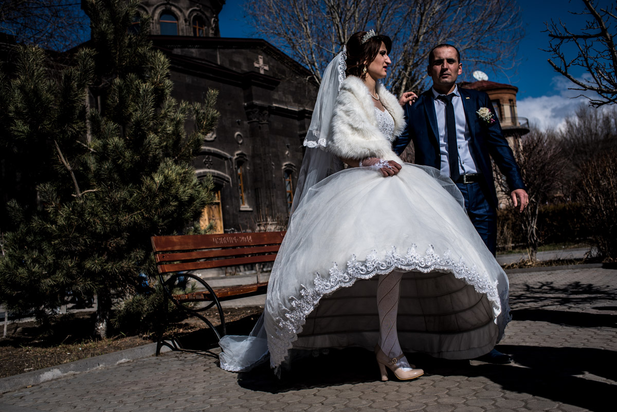 photograph of bride looking like she's on one leg after her wedding in church in gyumri in armenia