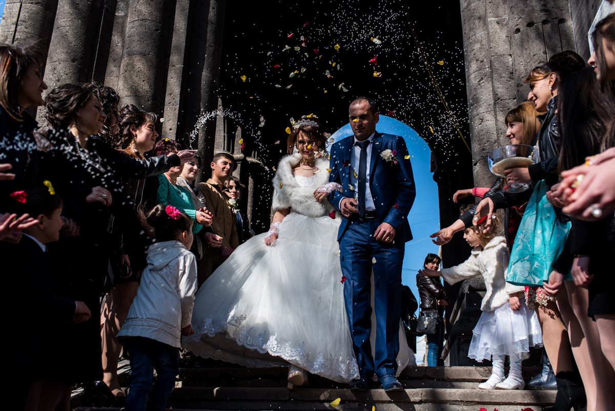 confetti is thrown over bride and groom after their church wedding ceremony in armenia