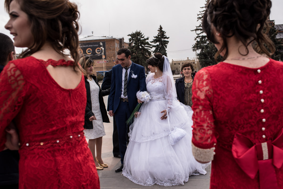 bride and groom and two ladies dressed in red are photographed in gyumri square after their wedding