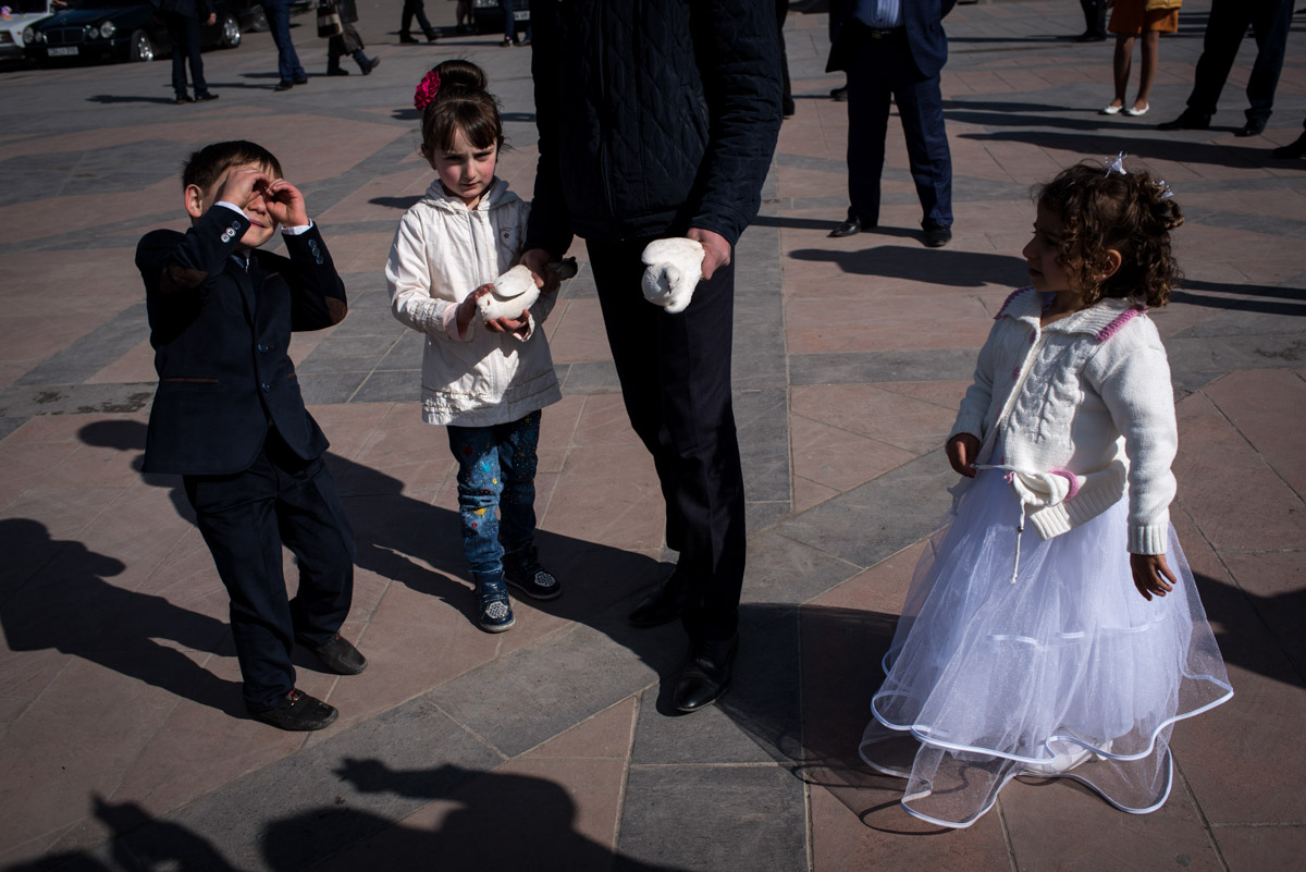 young children and white doves photographed after wedding ceremony in gyumri in armenia